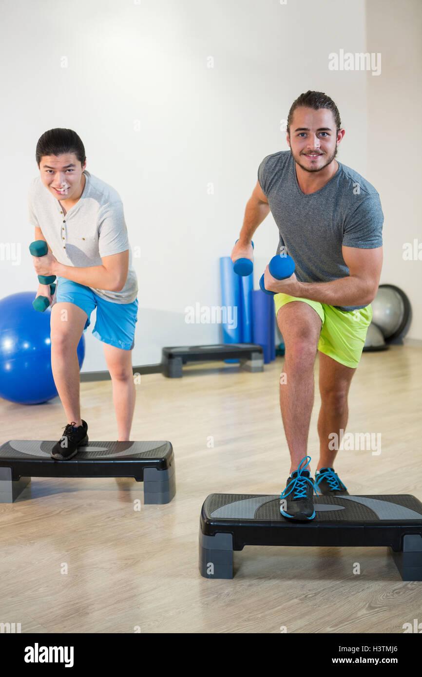 Zwei Männer, die Step aerobic Übungen mit Hantel auf stepper