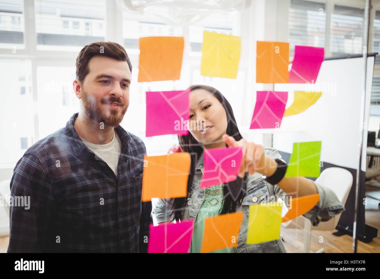 Geschäftsleute, die am Multi farbige Kurznotizen auf Glas Stockbild