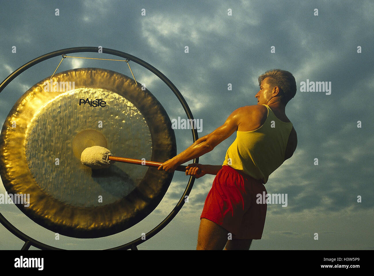 Mann, Gong, Hit, Signal, Ton, Kultur, Tradition, in Chinesisch, asiatisch, Hammer, Schlag, groß, rund, Messing, Stockbild