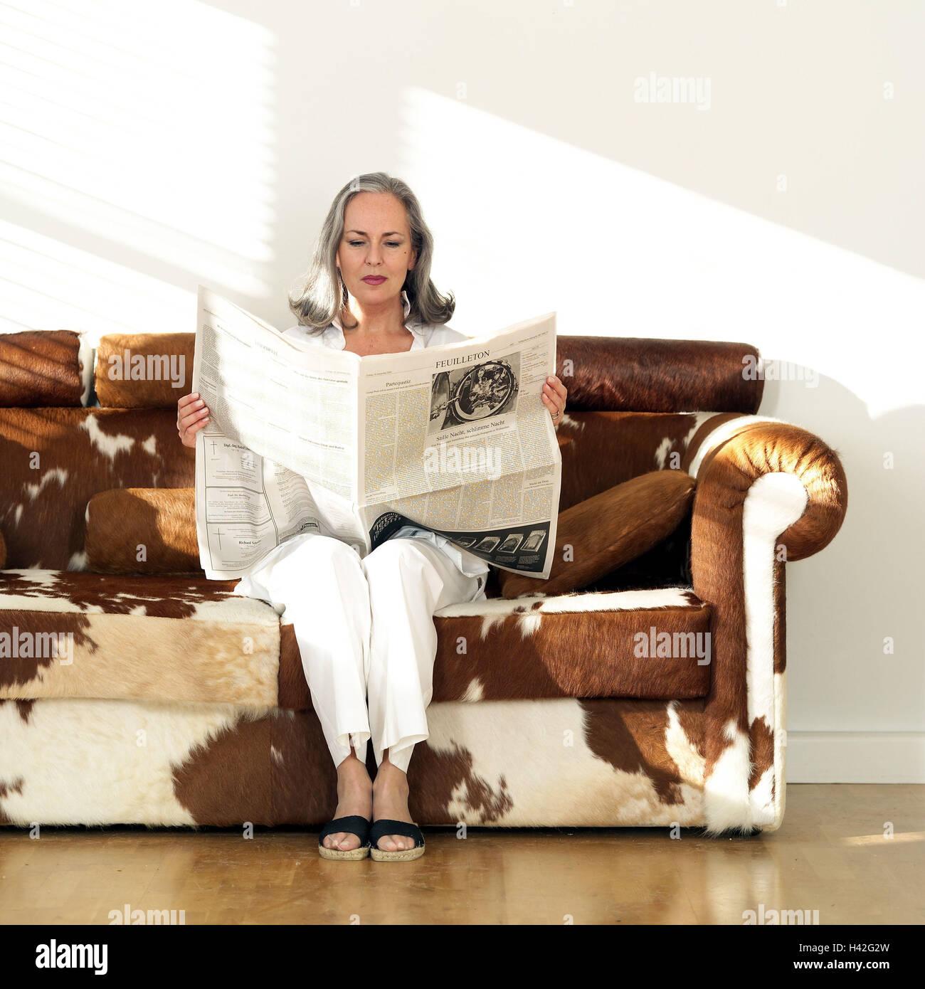 Kuhfellmöbel wohnzimmer sofa senior tageszeitung liest sitzt frau gut 50 60
