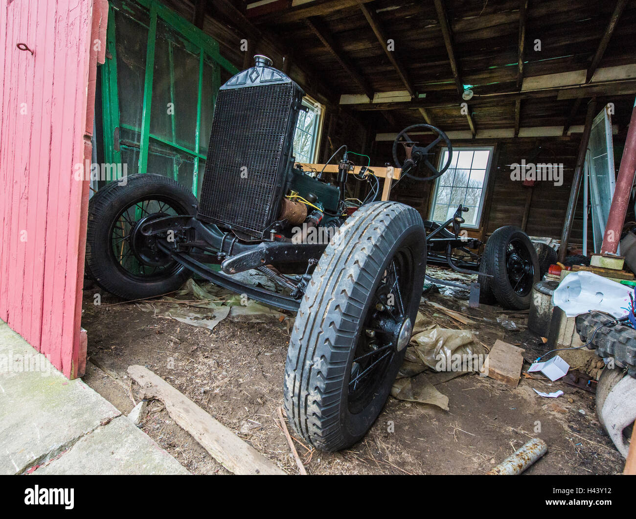 Ein Rahmen und Motor von einen Ford Model A sitzt in einer Scheune ...