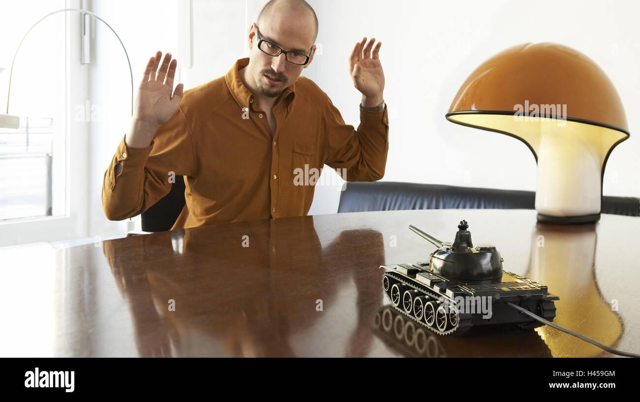 Mann, Brille, ernst, Hände hoch, Spielzeug Panzer, Bedrohung, Halbporträt, 20-30 Jahre, Brille, Bart, Stockbild