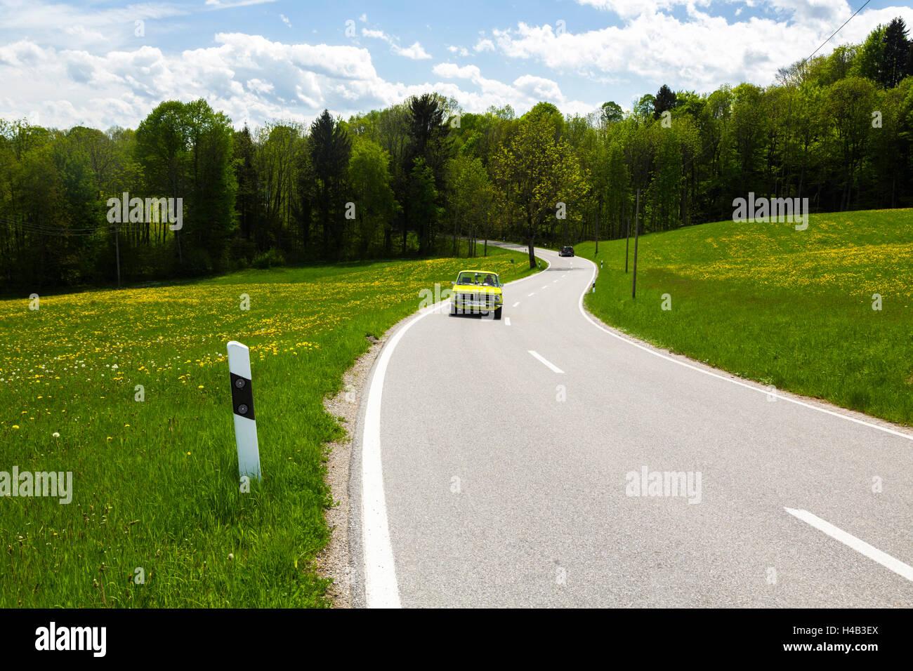 Deutschland, Bayern, grünes Auto fahren auf der Landstraße im Frühjahr Stockbild