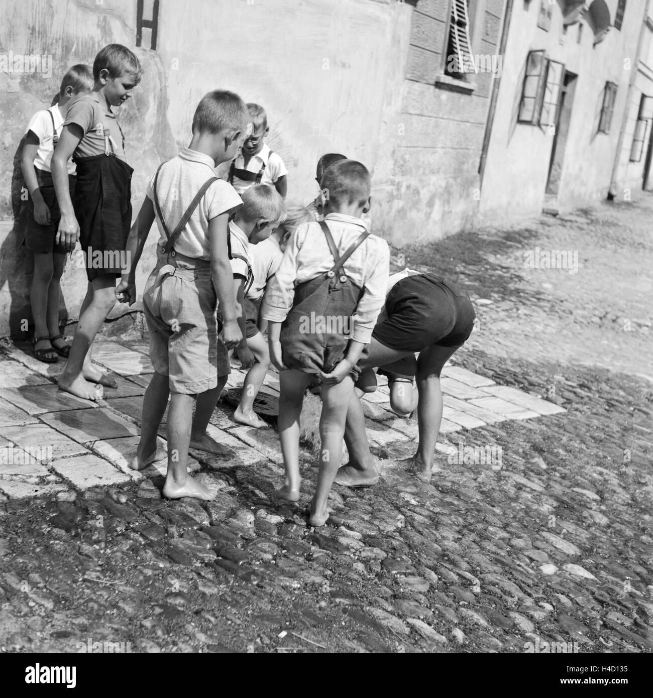 Kinder Spielen Auf der Straße Eines Dorfs in Österreich, Deutschland, 1930er Jahre. Kinder spielen auf Stockbild