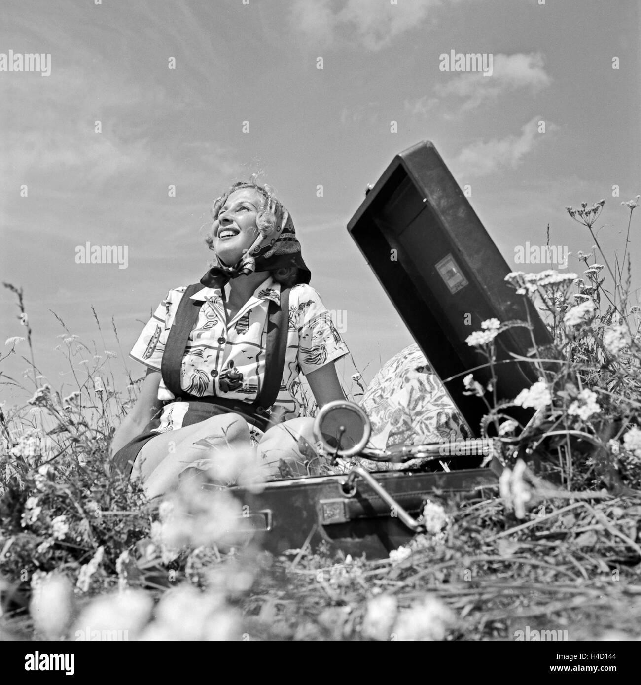 Eine Junge Frau Sitzt Mit Einem Grammophon in Einer Wiese Und Hört Musik, Deutschland, 1930er Jahre. Eine junge Stockbild