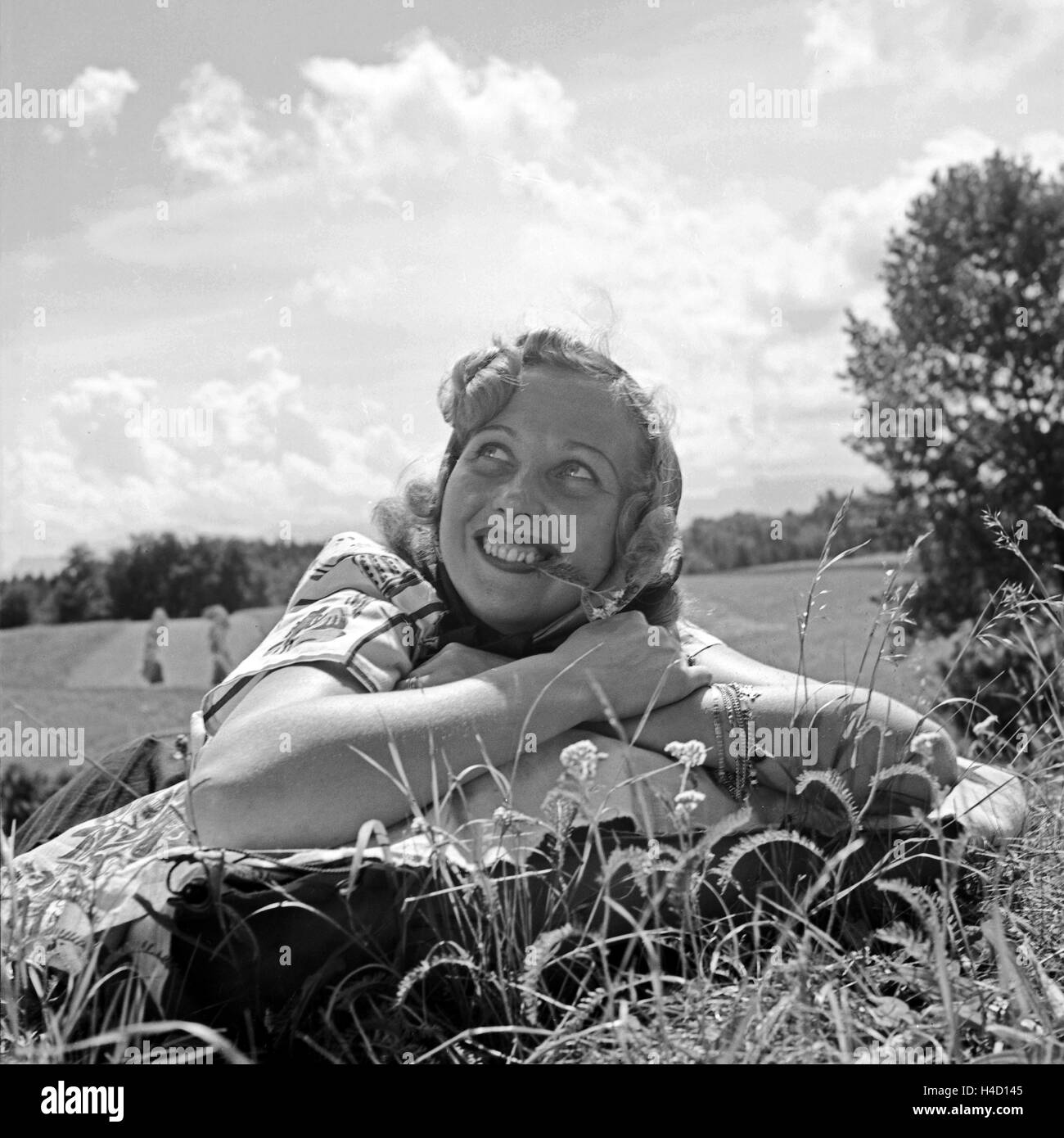 Eine Junge Frau so Lachen in Einer Wiese, 1930er Jahre Deutschland. Eine junge Frau auf der Wiese liegend lächelnd, Stockbild