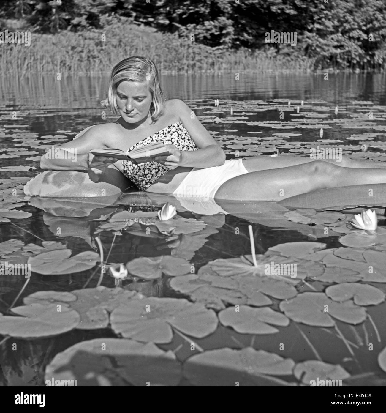 Eine Junge Frau Liegt Auf Einer Luftmatratze Inmitten Eines Seerosenteichs, 1930er Jahre Deutschland. Eine junge Stockbild