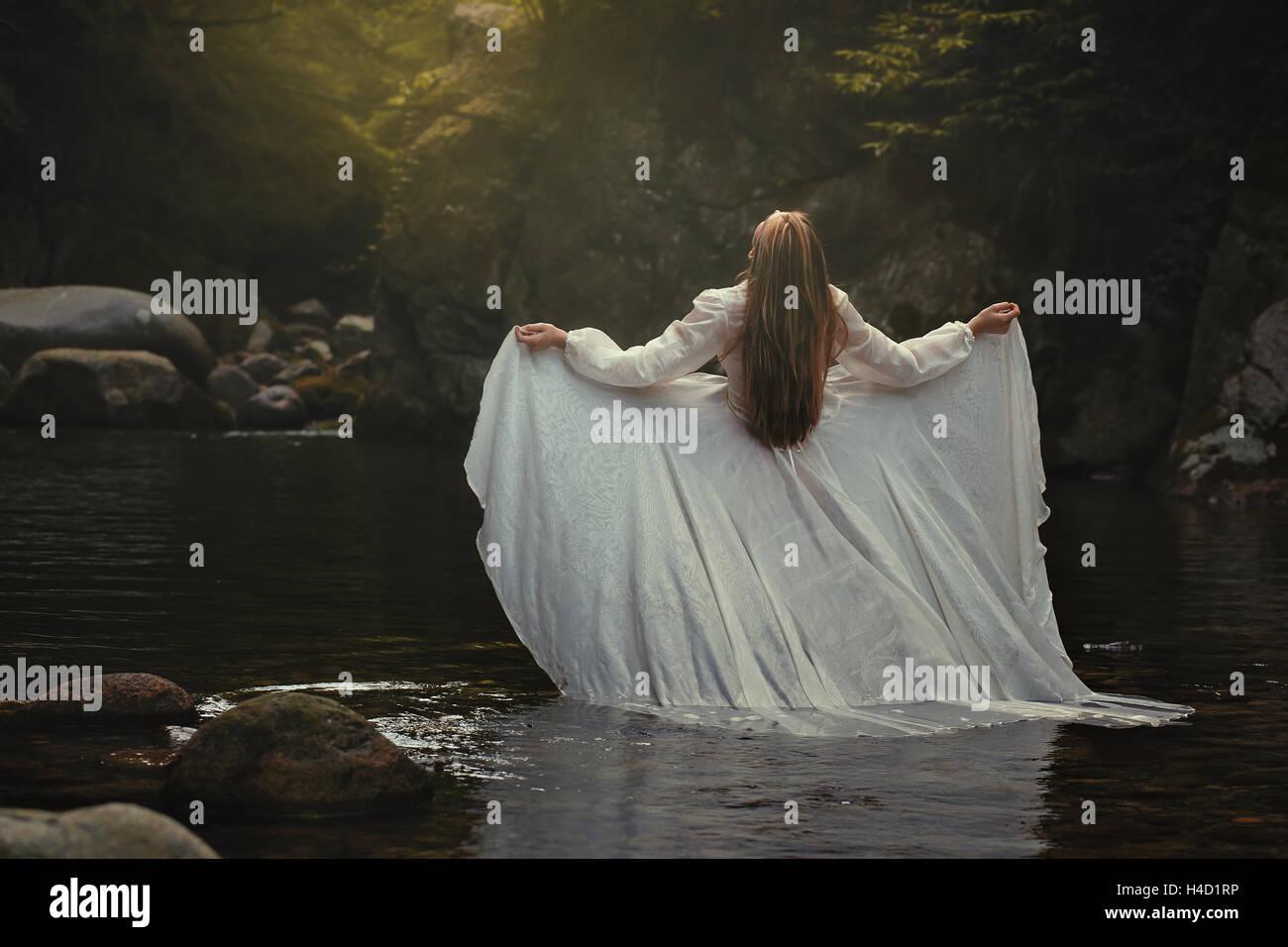 Ätherische Frau die Fluss-Musik hören. Surreal und romantisch Stockbild
