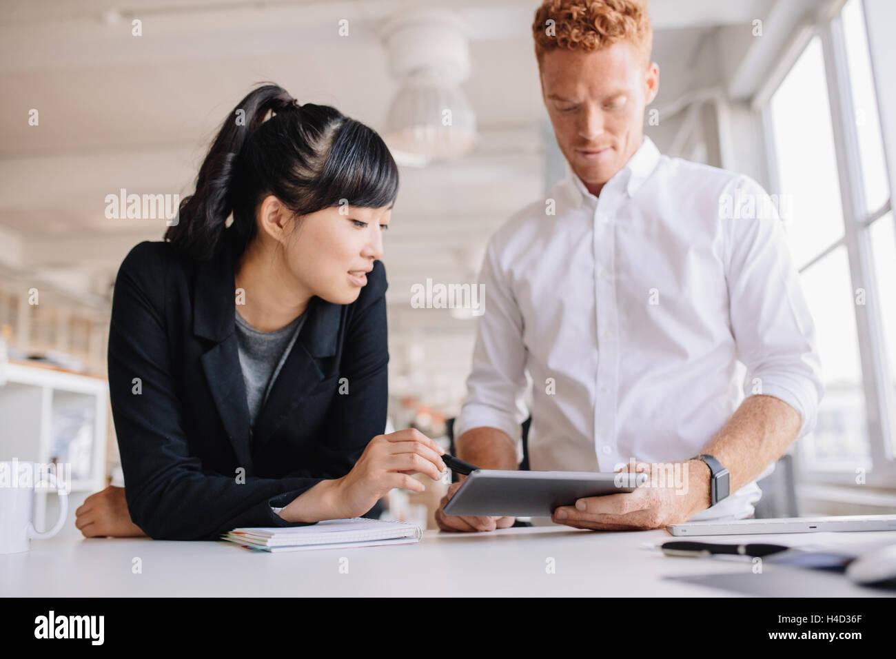 Geschäftsleute, die gemeinsam an digital-Tablette in modernen Büro. Business-Mann und Frau stehen am Schreibtisch Stockbild
