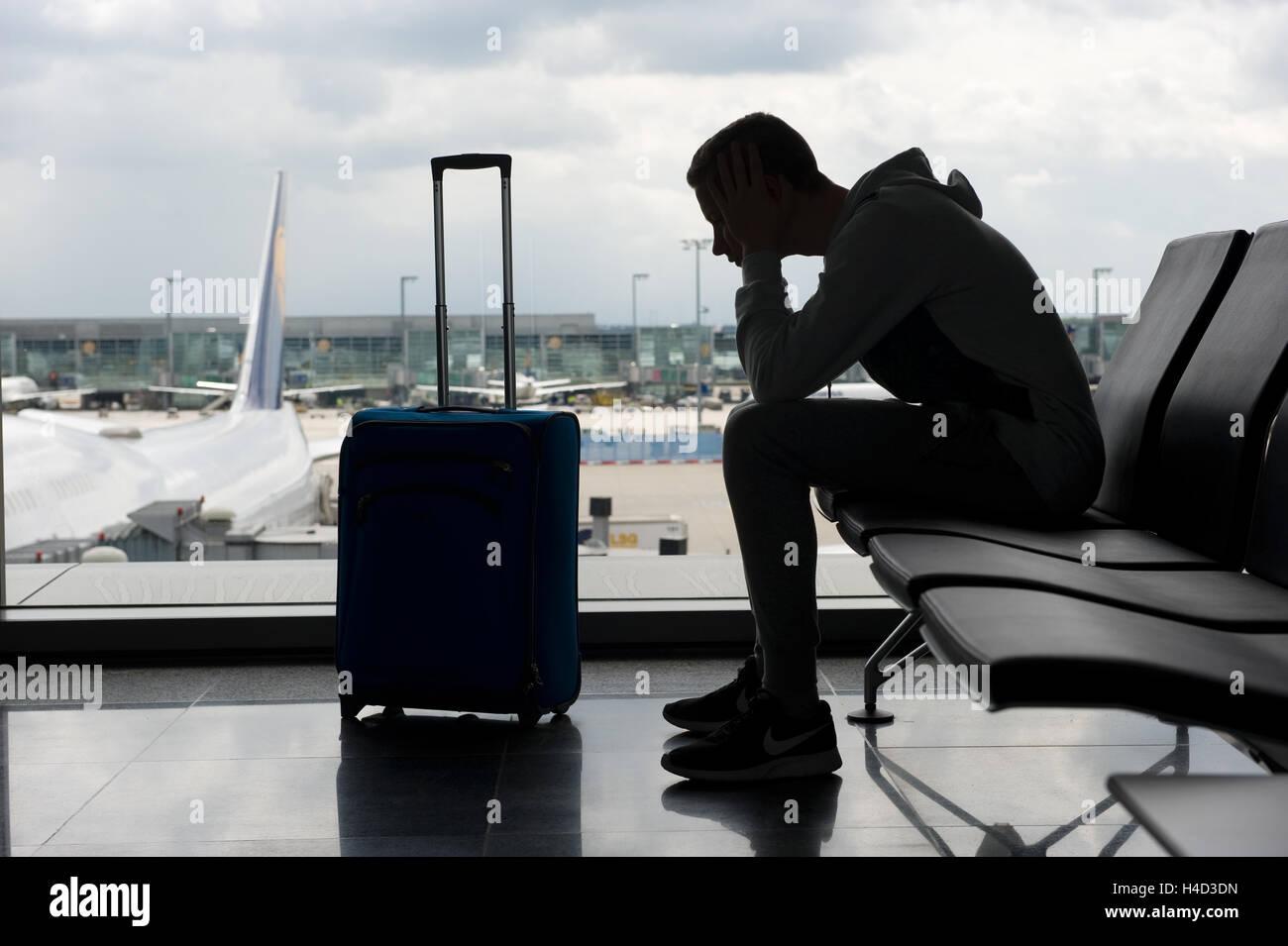 Ein Teenager wartet auf einem Flughafen für den Abflug Stockbild