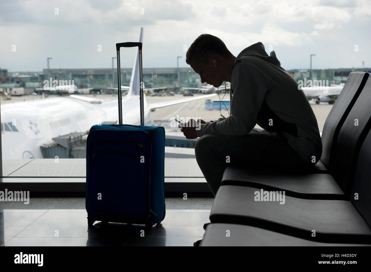 Ein Teenager wartet auf einen Flughafen und spielt mit seinem smartphone Stockbild