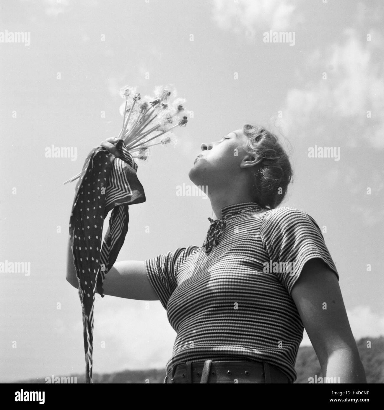 Eine Junge Frau Spielt Mit Löwenzahn, 1930er Jahre Deutschland. Eine junge Frau bläst die Samen des Löwenzahns, Stockbild