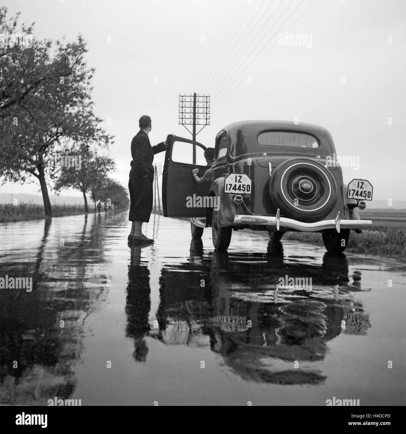 Mit Dem Ford V8 Auf Regennasser Fahrbahn, 1930er Jahre Deutschland. Mit dem Ford V8 auf einer nassen Straße, Stockbild