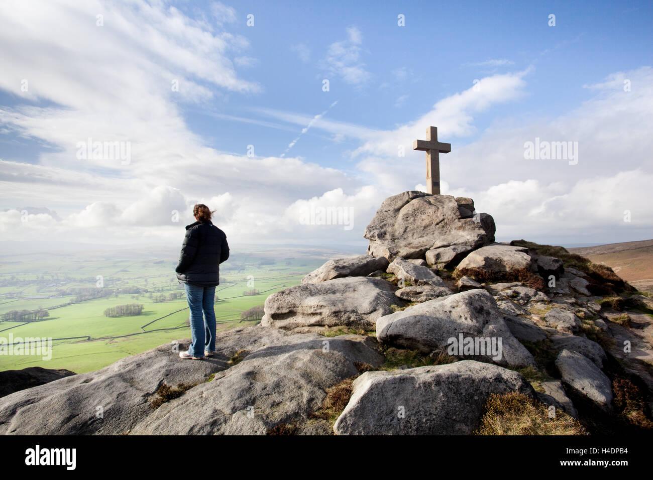Frau am Rylstone Cross, Kruzifix mit Blick auf den grünen Weiden am Rande der Yorkshire Dales, von einem Felsvorsprung Stockfoto