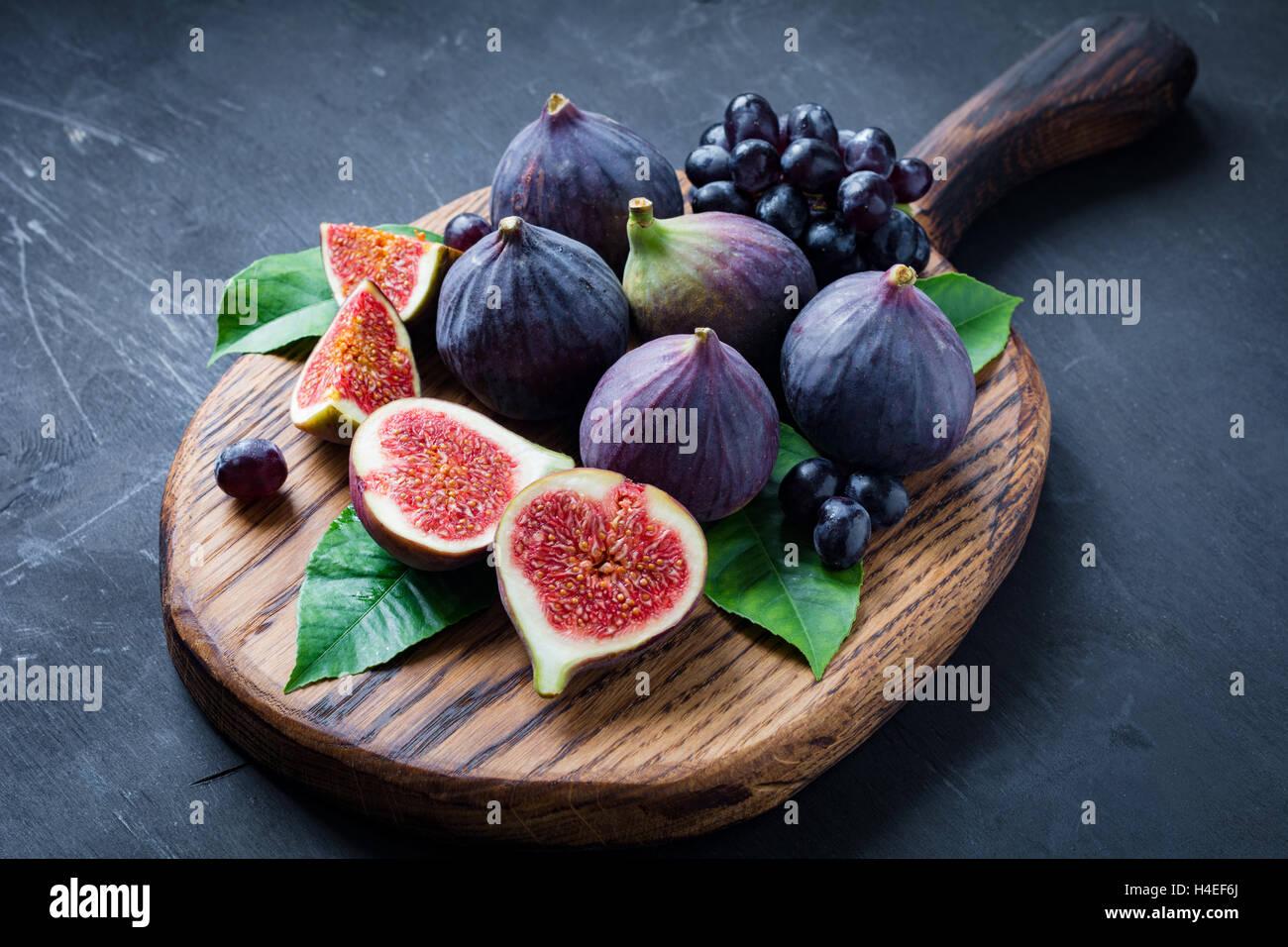 Obst-Teller: frische Feigen und schwarzen Trauben 'Isabella' auf Holzbrett. Horizontale Stockbild