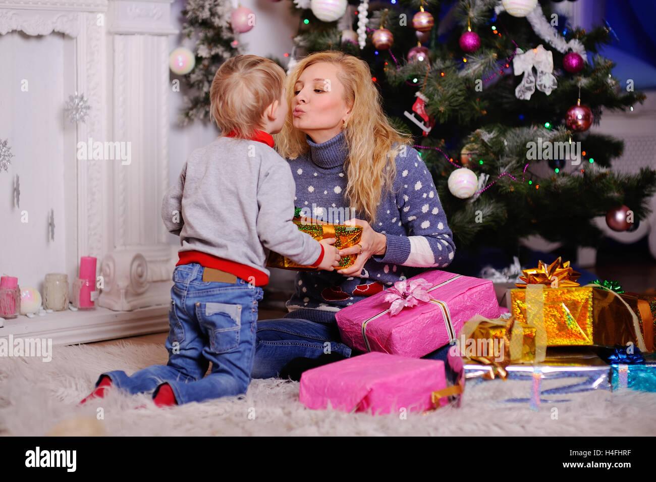 MOM gibt einem kleinen Kind ein Geschenk zu Weihnachten auf dem ...