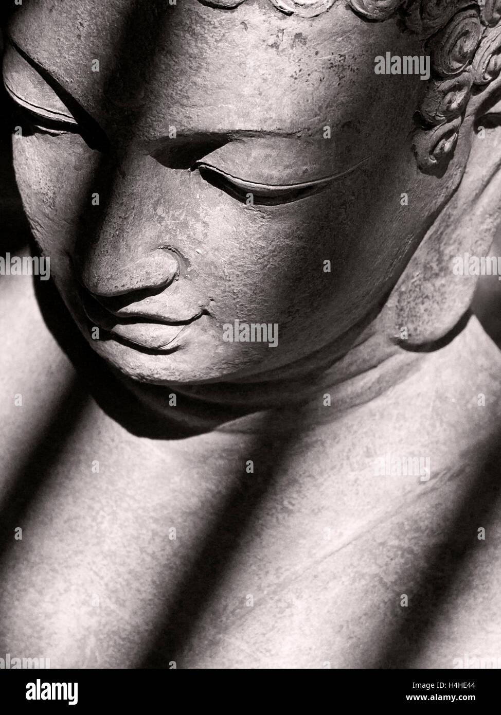 Kontemplative Studie der steinernen Statue des Buddha mit schrägen Schatten werfen, über Kopf und Schultern Stockfoto