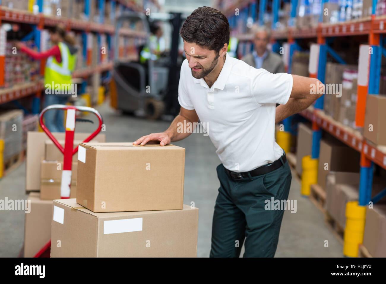 Männliche Arbeitnehmer leiden unter Rückenschmerzen während der Arbeit Stockbild