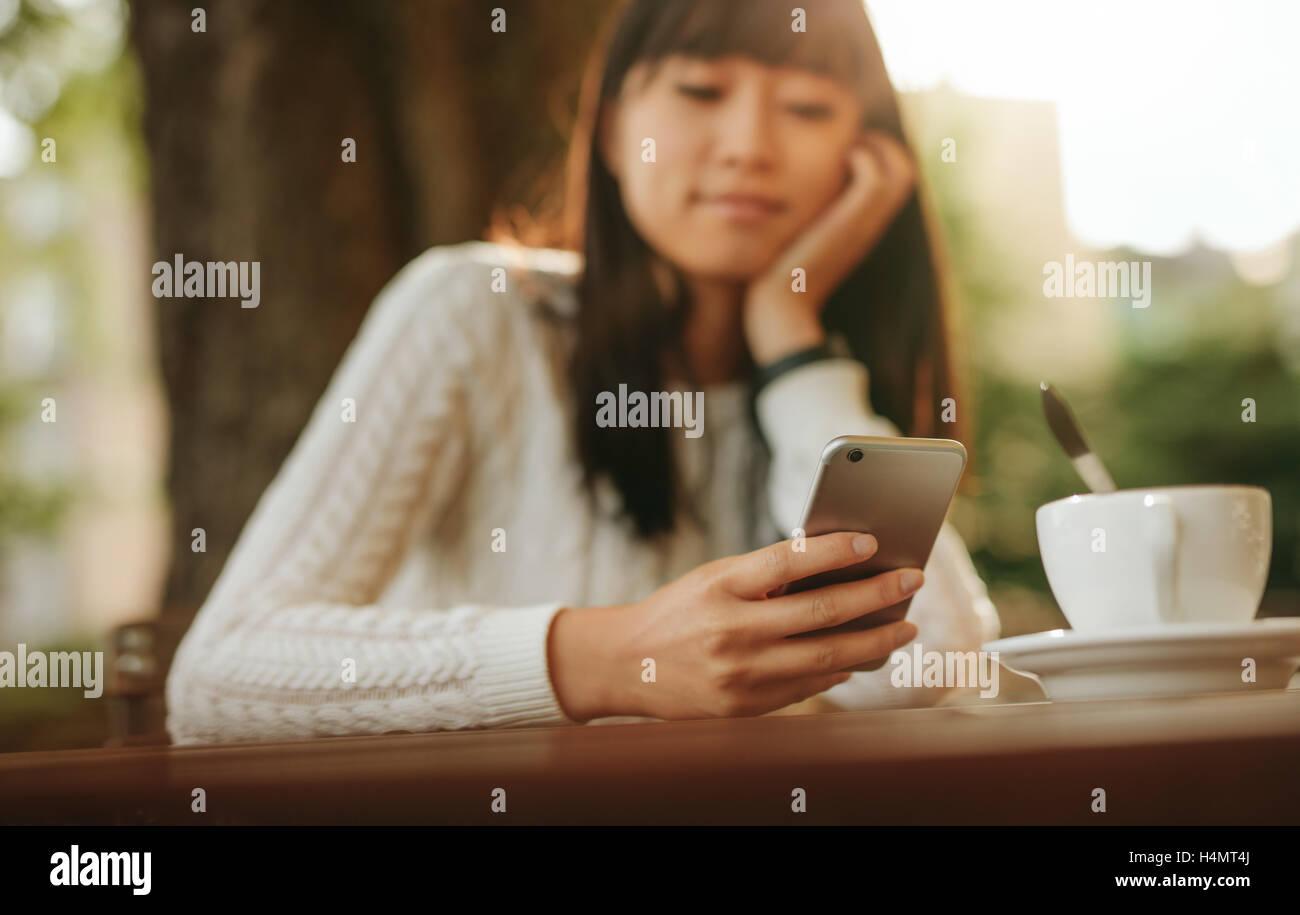 Junge Chinesin Blick auf Handy in der Hand beim Sitzen im Café im Freien. Asiatische weibliche Modell lesen Stockbild