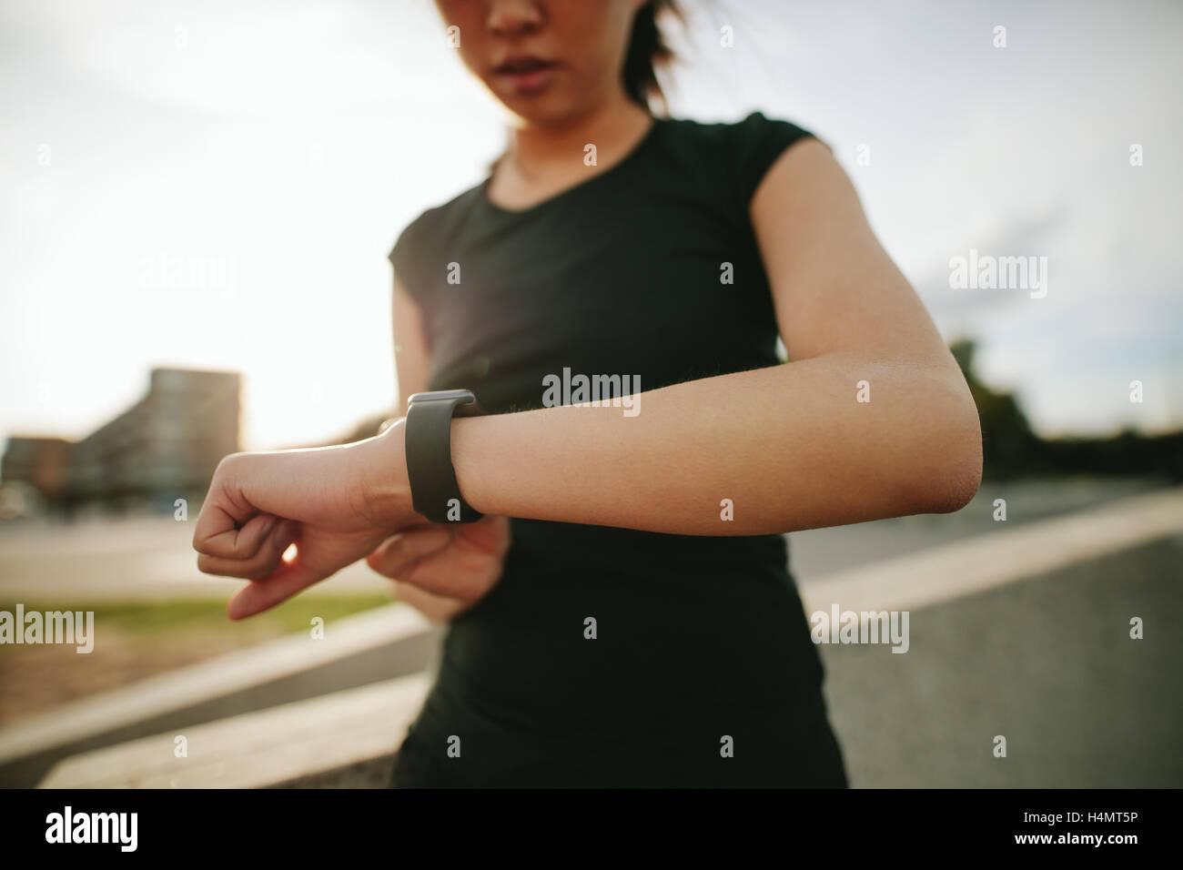 Schuss von junge Frau Läufer mit Smartwatch im freien hautnah. Fitness Frauen überprüfen ihre Leistung. Stockbild