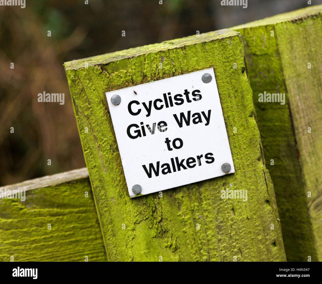 Ein Schild mit der Aufschrift Radfahrer Vorfahrt für Spaziergänger auf einem hölzernen Pfosten Stockbild