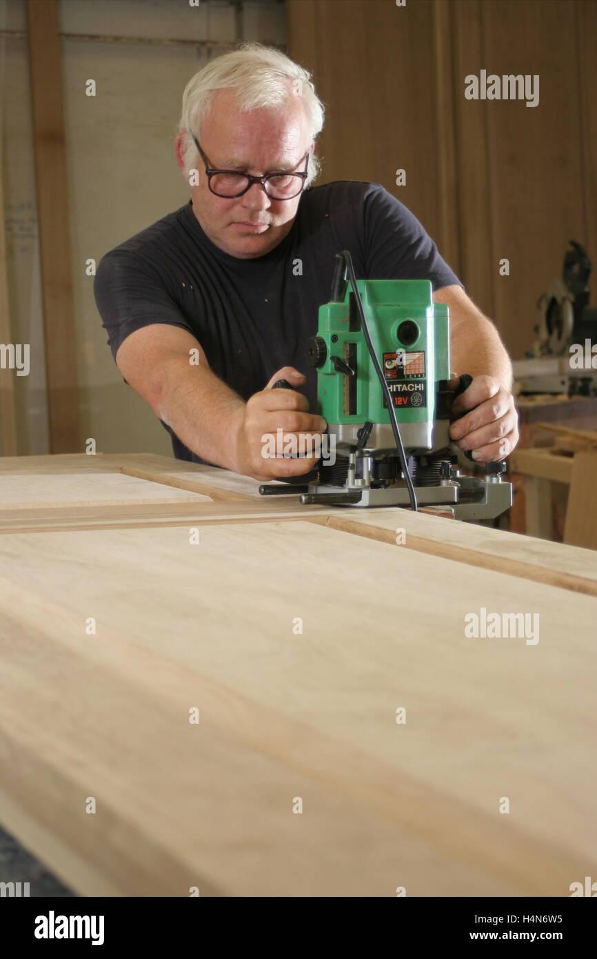 Ein Arbeiter in einer Tischlerei verwendet eine Fräsmaschine, einen ...