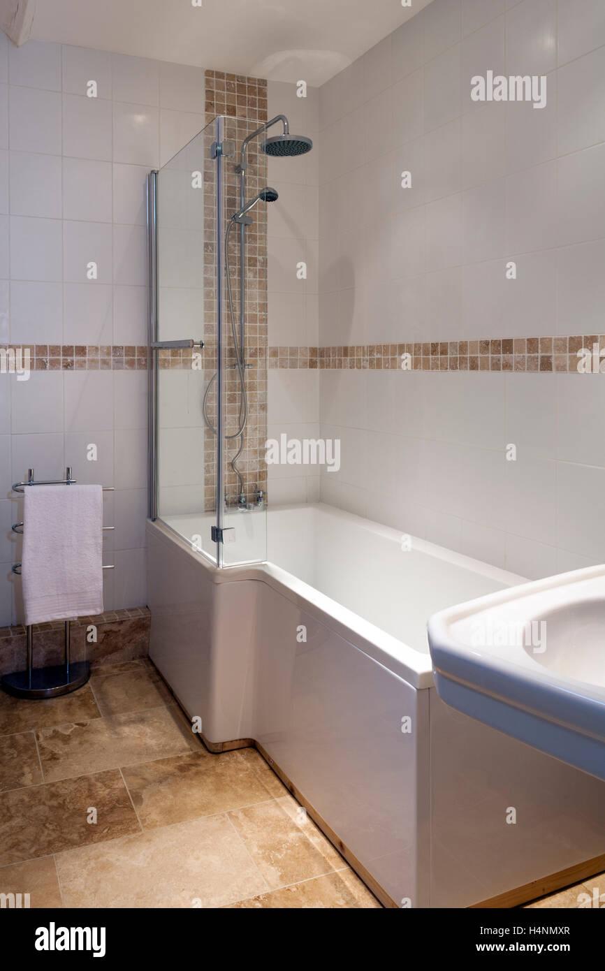 Eine moderne geflieste Badezimmer mit Badewanne mit Dusche über ...