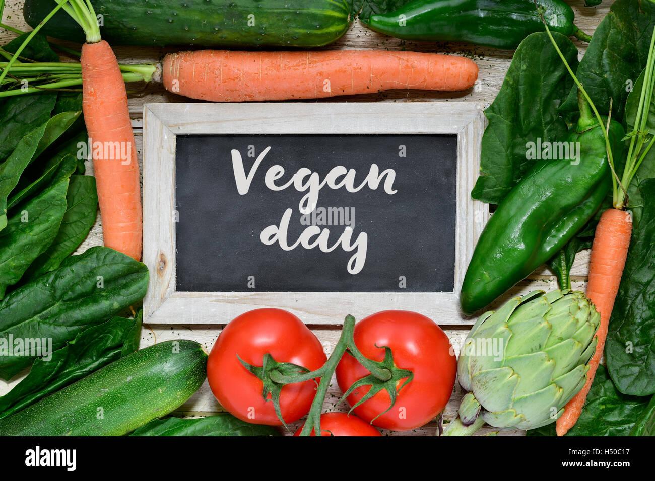 High-Angle Shot von einem hölzernen Oberfläche voller verschiedenen rohes Gemüse und eine Tafel mit Stockbild