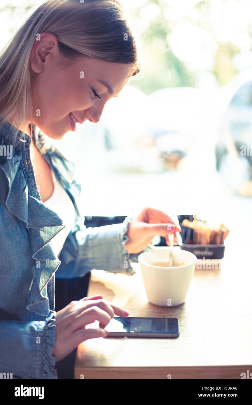Junge Frau Kaffee trinken und im Chat auf Handy Stockbild
