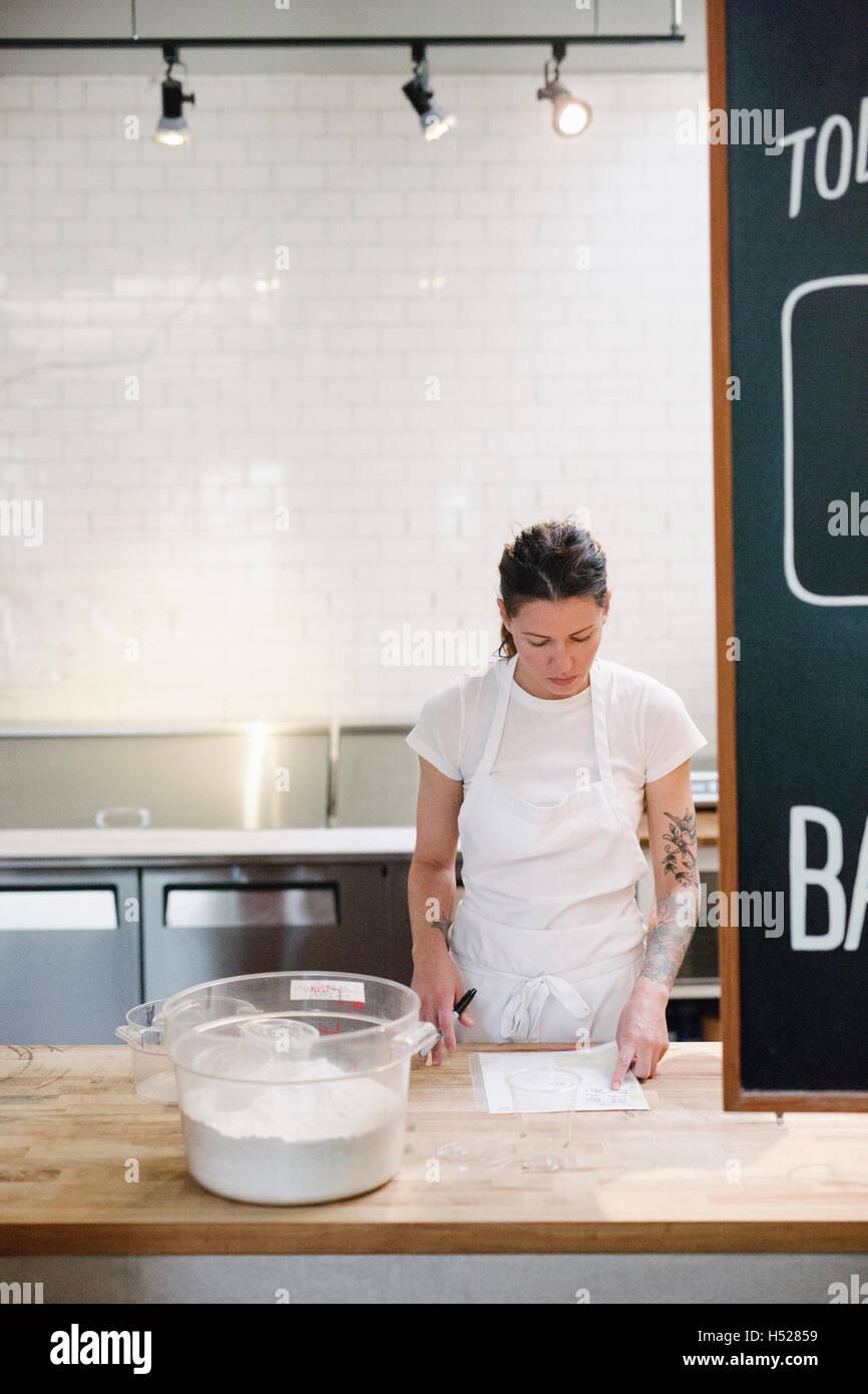 Frau trägt eine weiße Schürze an einem Schalter der Arbeit in einer Bäckerei. Stockfoto