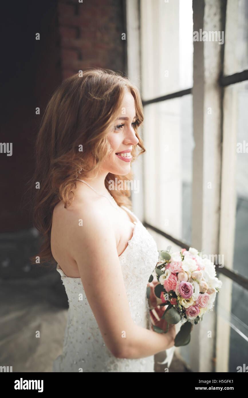 Elegante schöne Hochzeit Braut posiert in der Nähe von großen Fensterbogen Stockbild