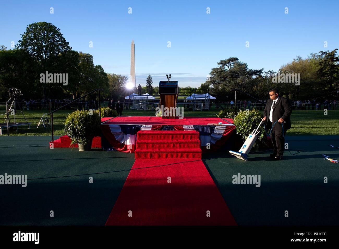 Ein Mitarbeiter des weißen Hauses saugt den roten Teppich, als letzten Vorbereitungen für die staatliche Stockbild