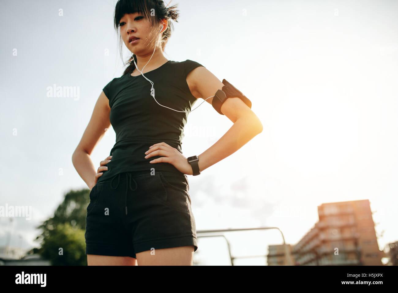 Schuss von junge Chinesin, die eine Pause bei einem Morgenlauf. Fitness Frauen stehen im Freien mit ihr Hände Stockbild