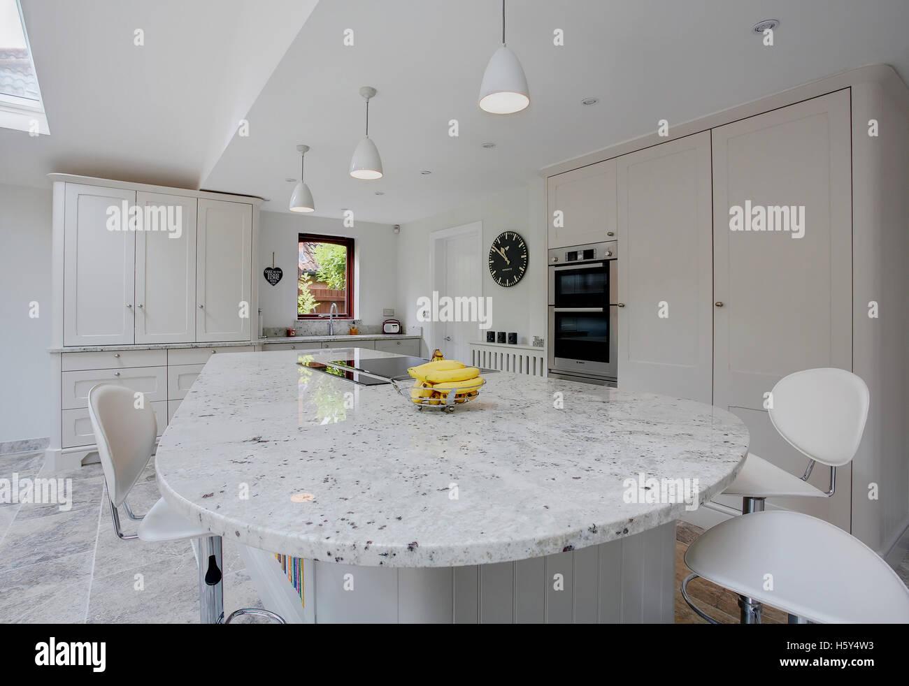 Eine moderne weiße Küche mit Granit-Arbeitsplatten in Großbritannien ...