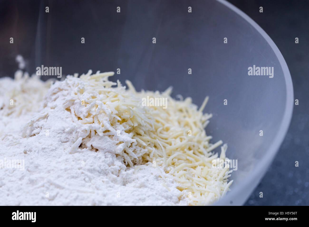 Eine Mischung aus Mehl und Käse in eine Schüssel geben, seine Zutaten für verschiedene Rezepte kochen. Stockbild