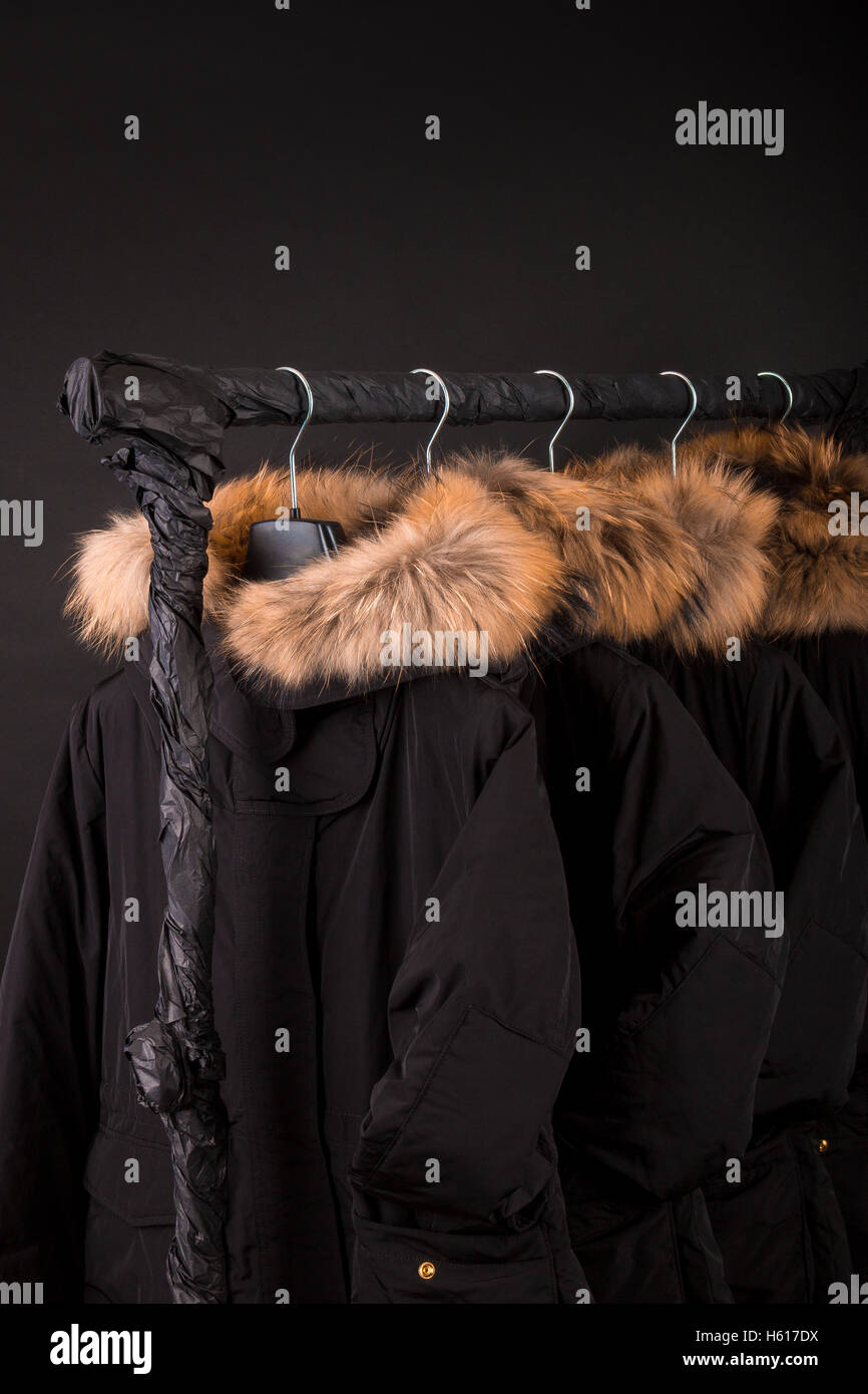 51af50ee129f Viele schwarze Mäntel, Jacke mit Fell Kapuze Kleiderständer hängen ...