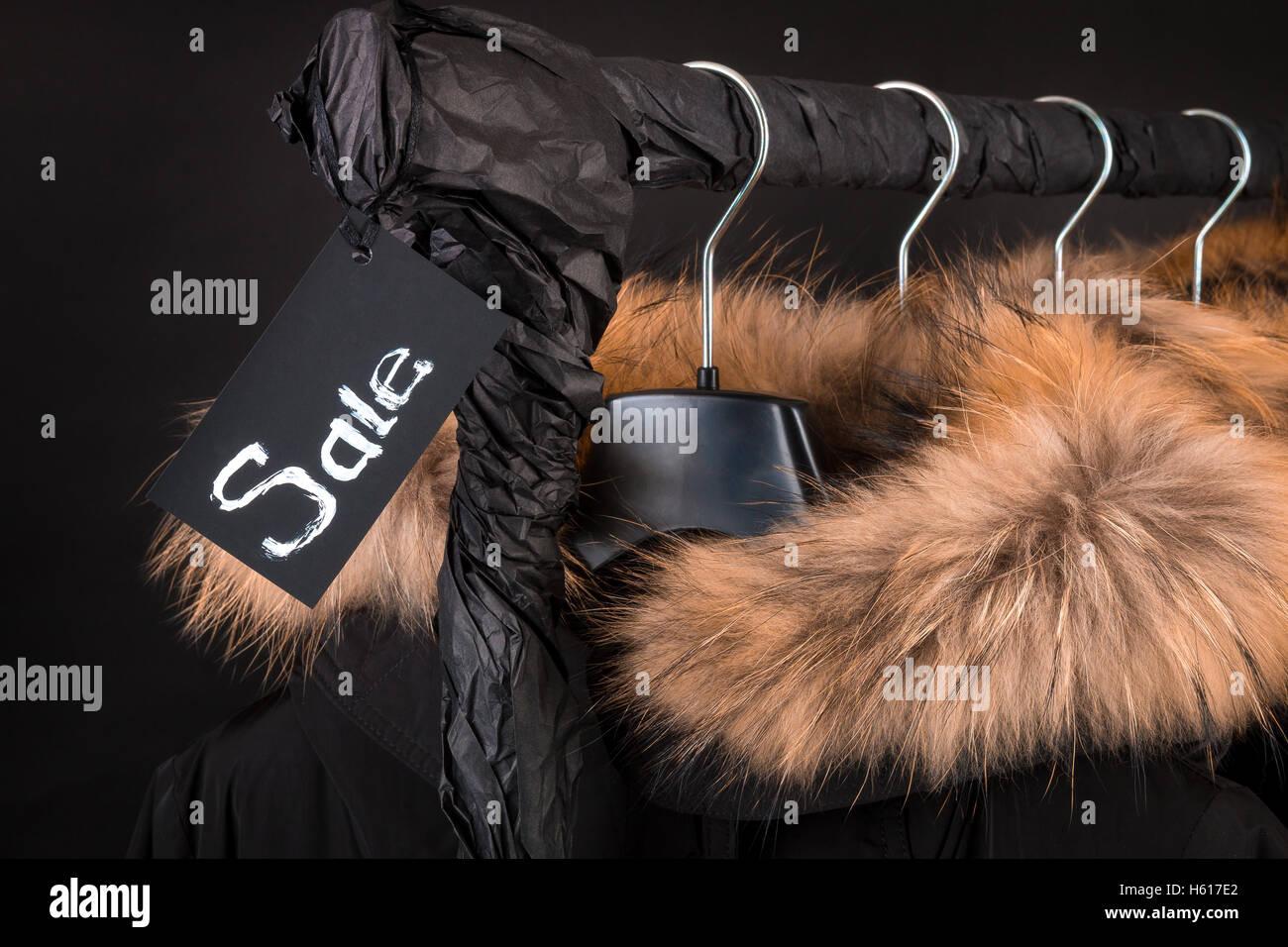 25203ffd4505 Viele schwarze Mäntel, Jacke mit Fell Kapuze Kleiderständer hängen.  Schwarzer Hintergrund. Verkauf-Inschrift. Schwarzer Freitag. Nahaufnahme