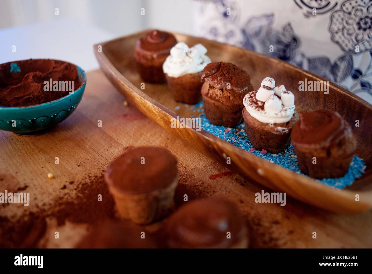 Kochen, Cupcakes, Muffins und einen Teller mit Zutaten für die Dekoration auf dem Tisch Stockfoto
