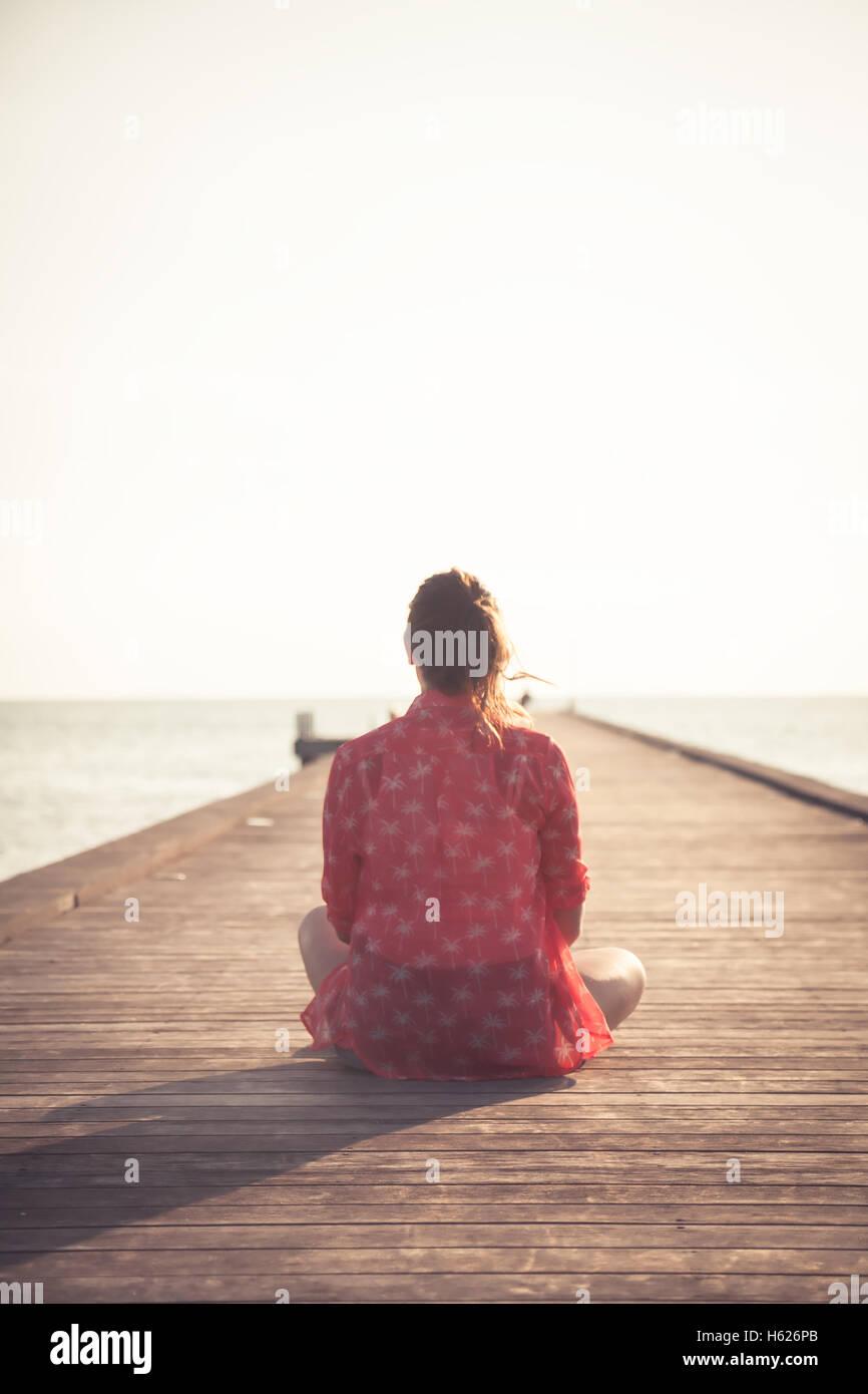Nachdenkliche Frau Touristen sitzen auf Holzsteg am Strand bei Sonnenuntergang und Blick auf Infinity-Blick in Richtung Stockbild