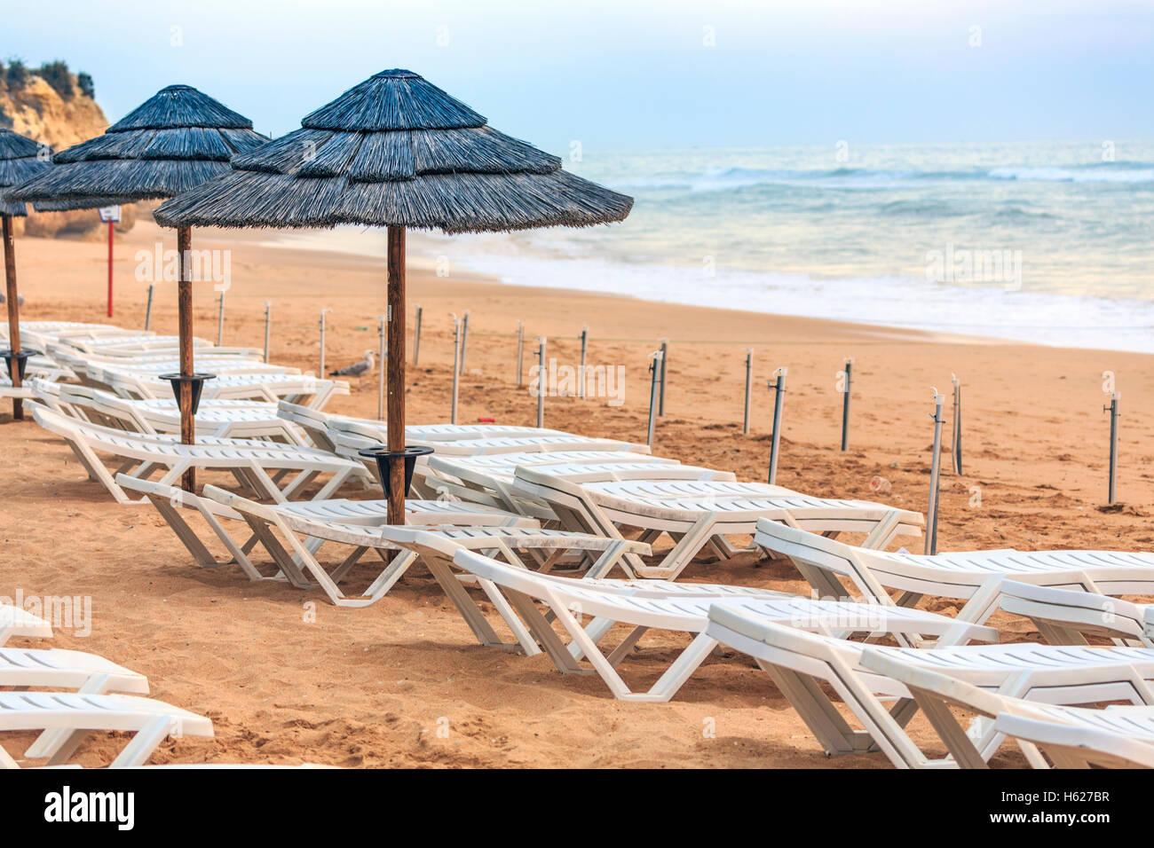 Albufeira Algarve Portugal leer Sonnenschirmen und Stühlen Bett machte das Meer im Hintergrund Abenddämmerung Stockbild
