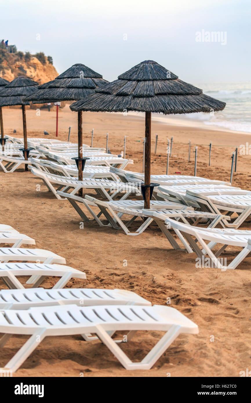 Oura Albufeira Algarve Portugal leeren Strand Sonnenschirme und liegen Bett machte das Meer im Hintergrund Dämmerung Stockbild