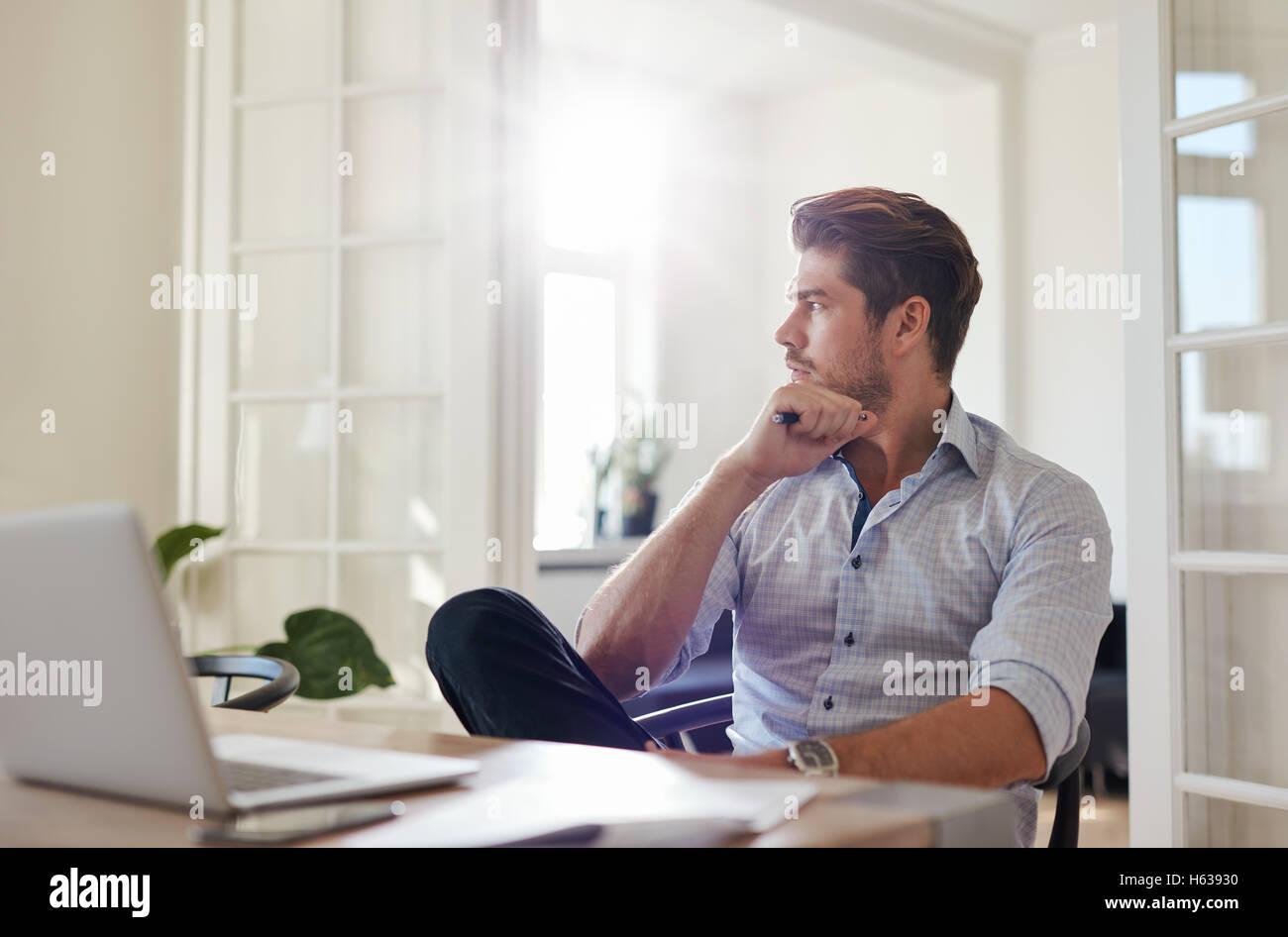 Aufnahme des jungen Mann am Tisch wegschauen und denken. Nachdenklich Geschäftsmann sitzen home-Office. Stockbild