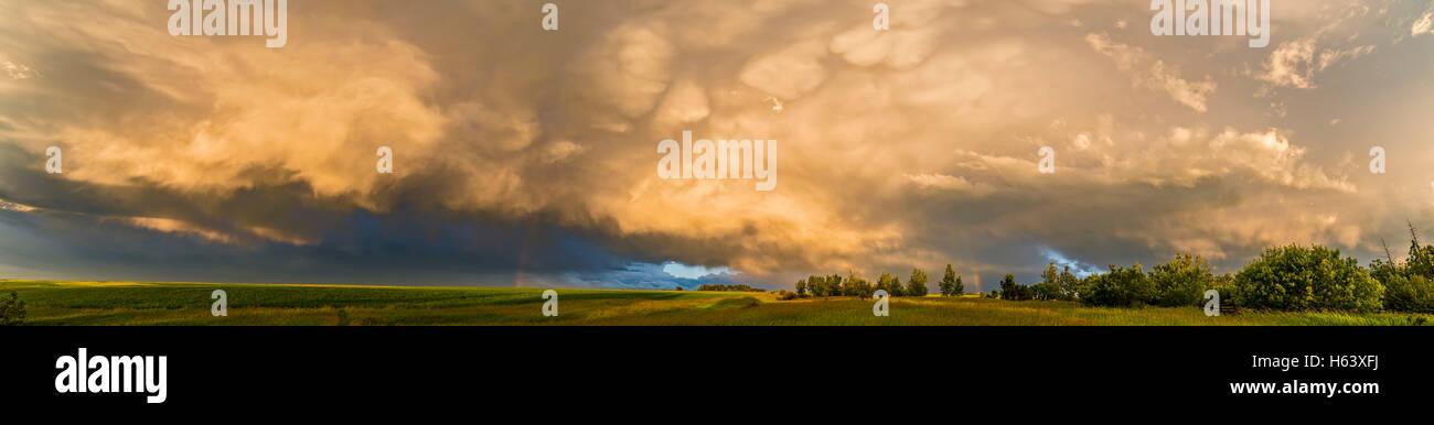 Ein Wolkengebilde ein Gewitter und Regenbogen Fragmente vor dem Hintergrund der niedrigen Sonne von zu Hause im Stockbild