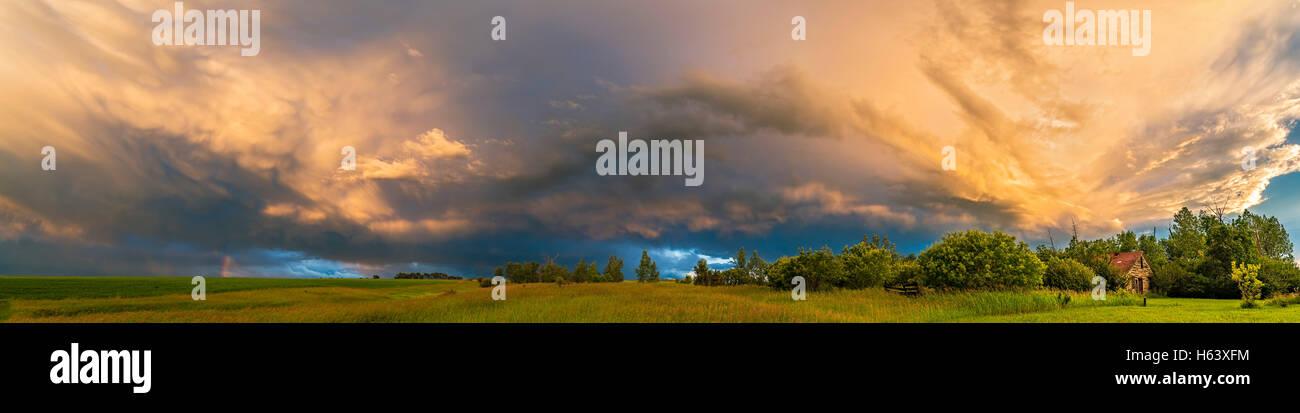 Ein Wolkengebilde ein Gewitter und Regenbogen Fragment vor dem Hintergrund der niedrigen Sonne von zu Hause im Süden Stockbild