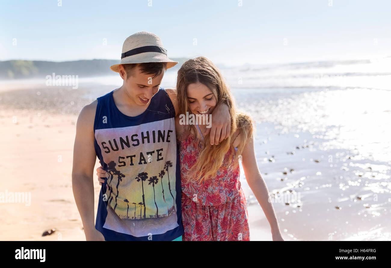 Glückliches junges Paar in Liebe zu Fuß am Strand entlang Stockfoto