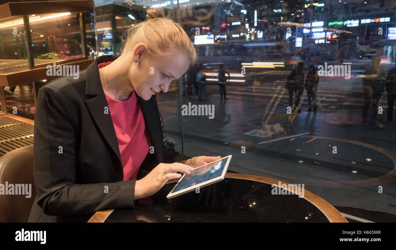 Frau mit Pad im Café durch Fenster mit Blick auf die Stadt Stockbild