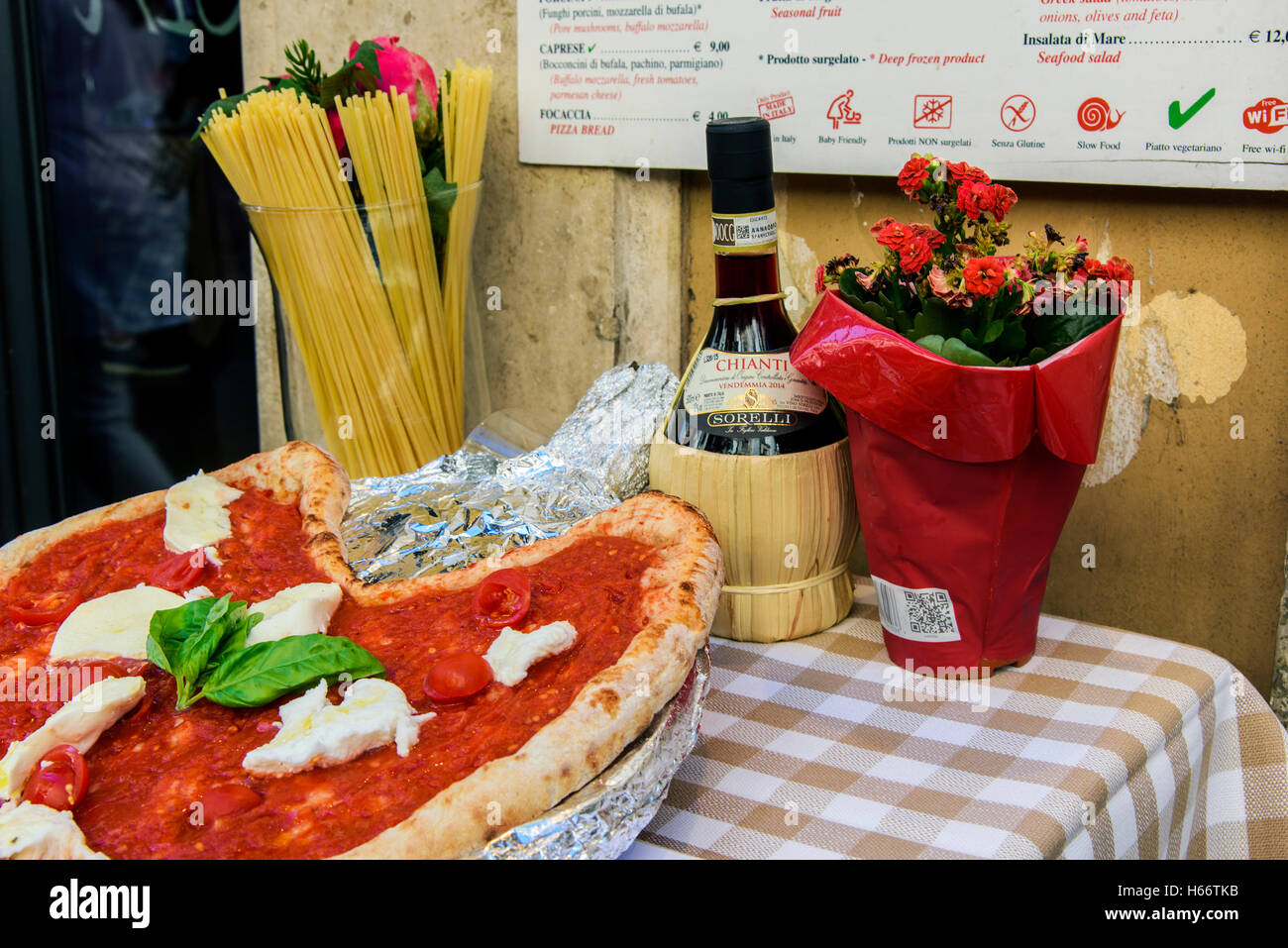 Pizza Margherita, Spaghetti und Flasche Chianti Rotwein auf einem Tisch vor einem Restaurant in Rom, Latium, Italien Stockbild