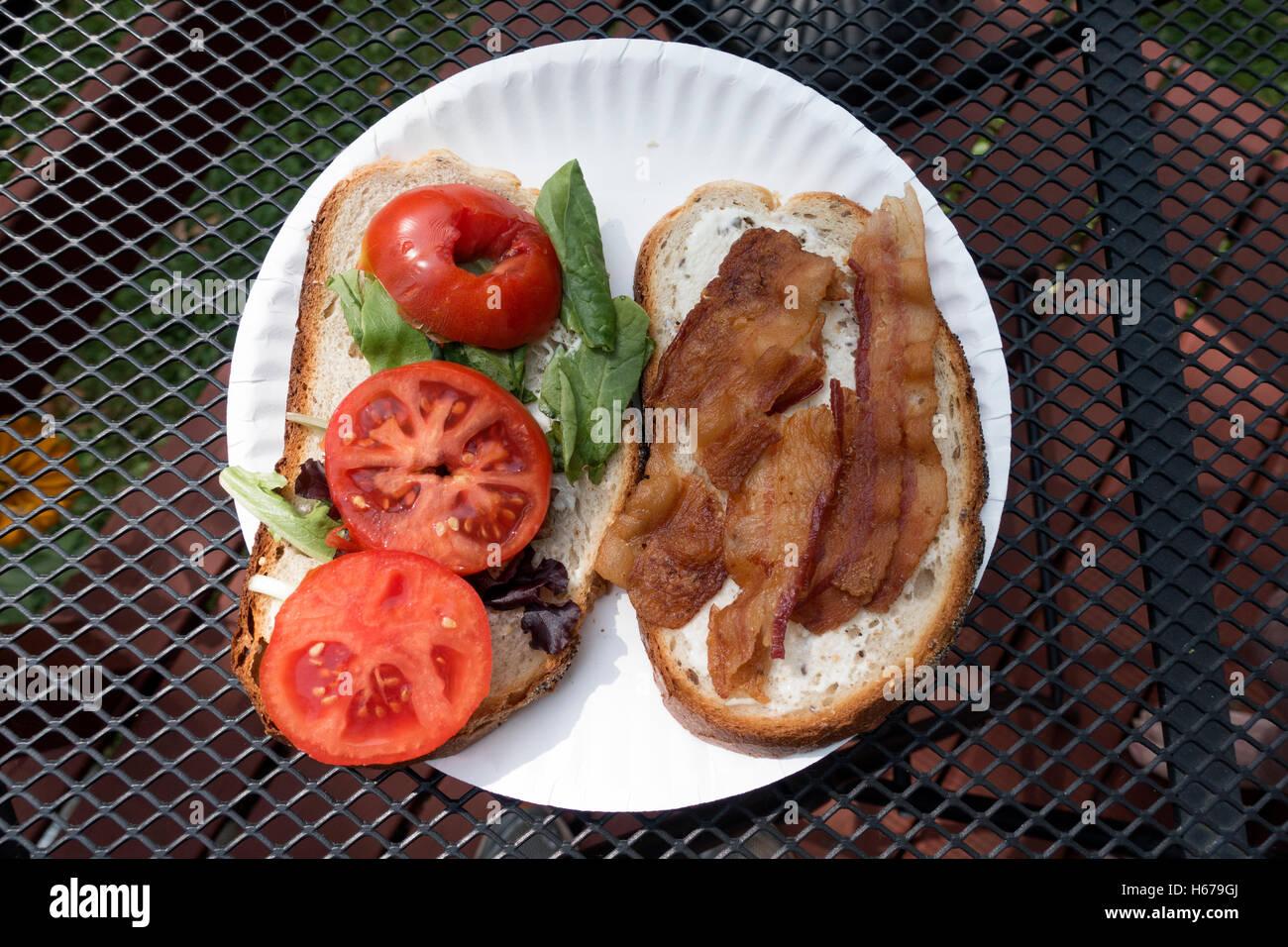 Speck, Salat und Tomate BLT Sandwich öffnen konfrontiert, auf einem offenen Gitter Tisch draußen serviert. Stockbild