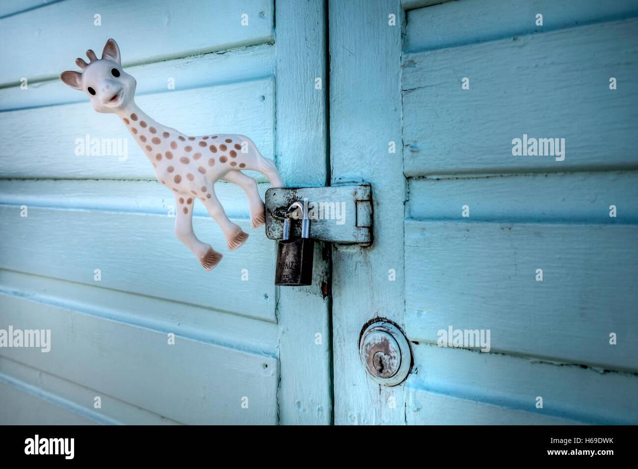 ein Spielzeug Giraffe hängt an einem Pad verschlossene Tür Stockbild