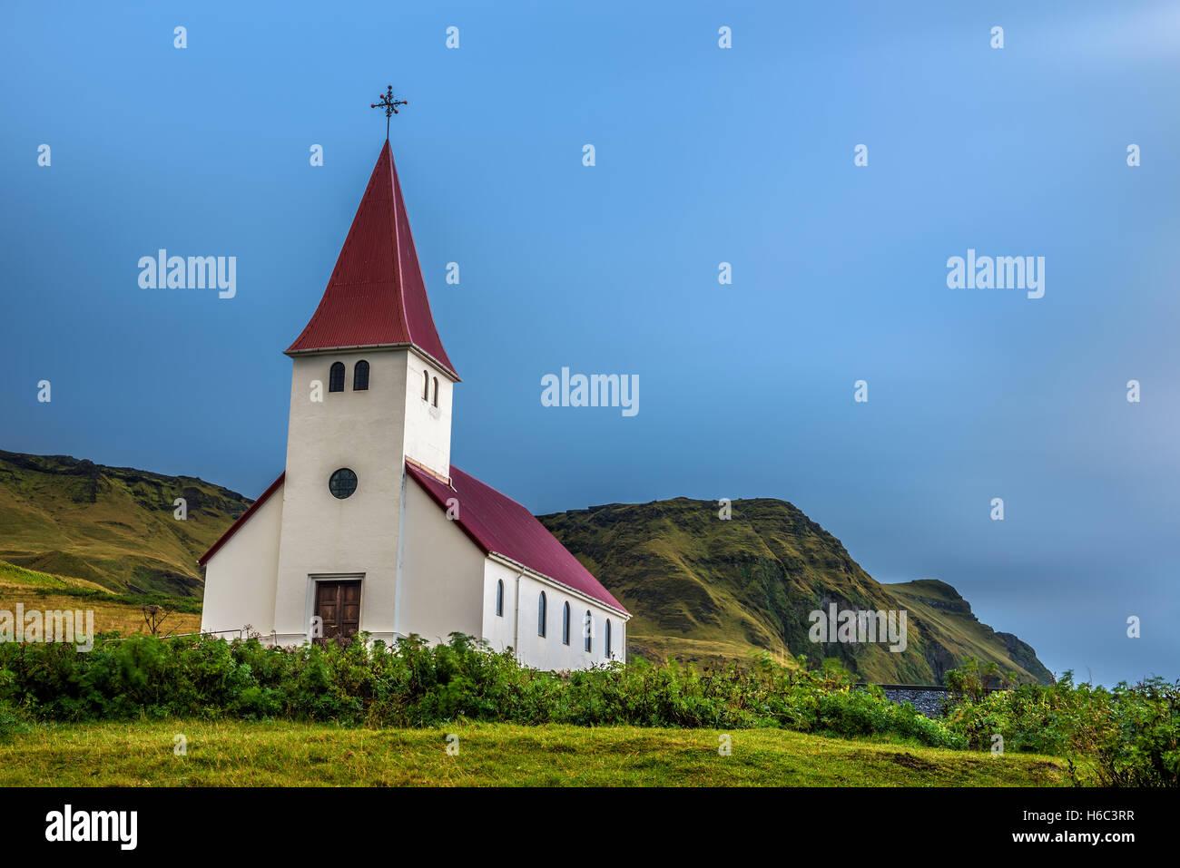 Schwere Wolken über der lutherischen Kirche auf einem Berg in die Stadt Vik in Island. Langzeitbelichtung. Stockbild